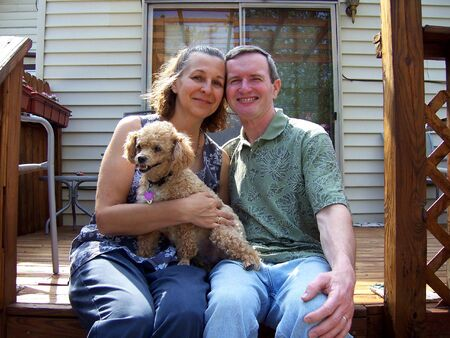 miniature people: a happy middleage couple with pet poodle