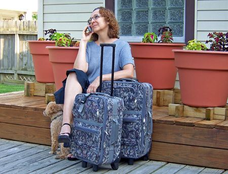middleage woman on cell phone with pet and luggage photo