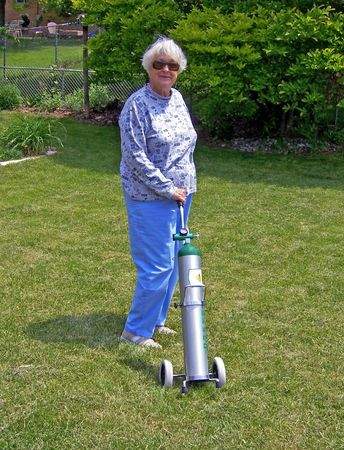 portable: senior lady with portable oxygen tank in backyard
