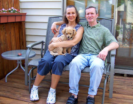 a happy middleage couple with pet poodle photo