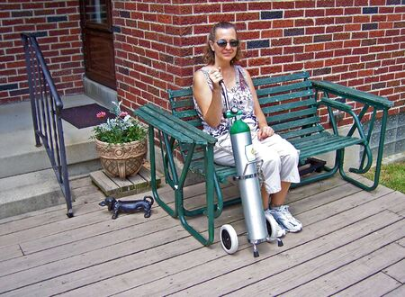 portables: a middleage lady with portable oxygen tank  Stock Photo
