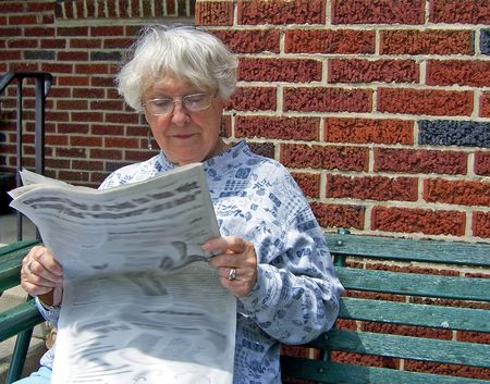 reading glasses: senior woman reading newspaper on outdoor bench Stock Photo