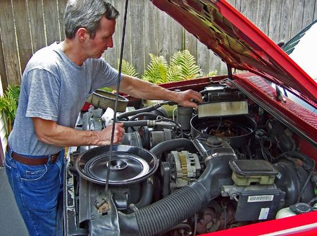 middleage man changing air filter on car Stock Photo