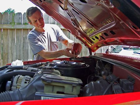 a middleage man adding oil to car