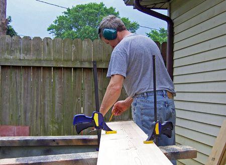 residental: a man marking cut line on lumber