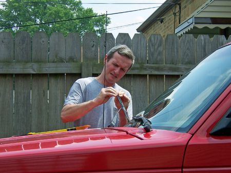 middleage man changing windshield wipers on car