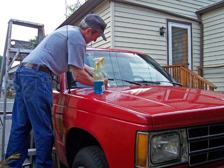 a middleage man cleaning windshield of car Stock Photo - 1237082