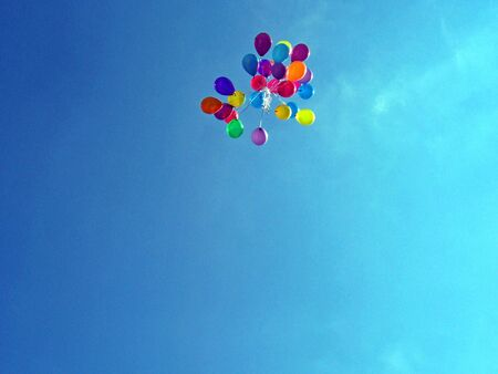 bunch of bright colored balloons released in sky  Stock Photo