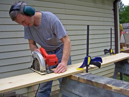 전동 공구로 목재를 톱질하는 남자