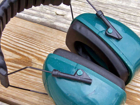 ear muffs: green ear protector muffs on wooden deck Stock Photo