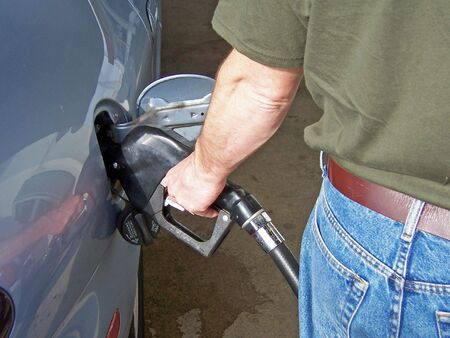 pumping gasoline into a car at a self serve gas station. photo