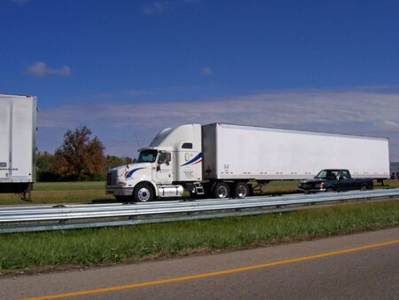 haul: semi trailer truck driving on divided highway Stock Photo