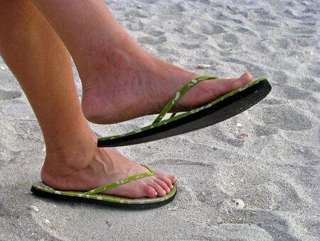 sandy feet with green sandals on beach Reklamní fotografie