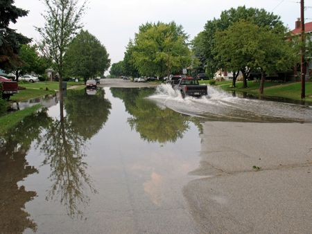 surge: residential city street flooded after heavy rain