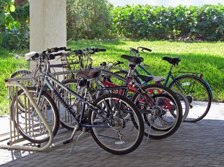 bicycles parked in bike rack under condo complex photo