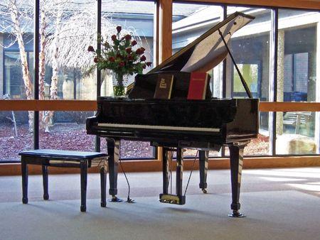 een piano tegen de ramen in huis salon
