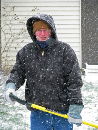 clearing the path: winter scene of a man shoveling snow Stock Photo