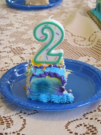 piece of birthday cake with number 2 candle Stock Photo