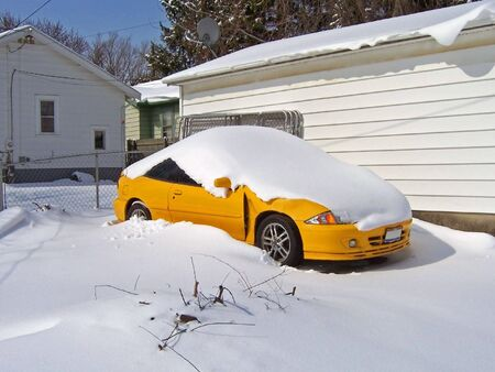 car covered with snow after winter storm.