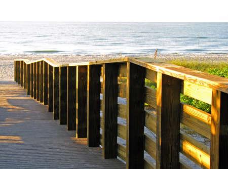 wooden boardwalk leading to the ocean beach photo