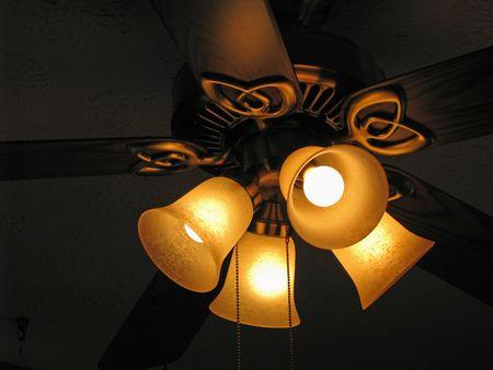 가 까이 서 천장 팬 전구를 밝게 조명