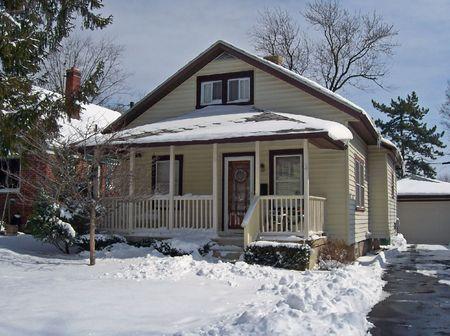cape cod home: snowy single  home in urban neighborhood Stock Photo