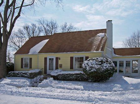 snowy single  home in urban neighborhood Stock Photo