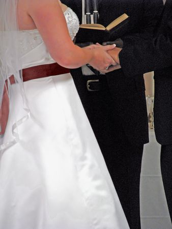 chaplain: wedding couple holding hands during marriage ceremony