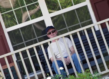 middle age man sitting on front porch photo