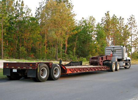 flatbed truck: flatbed semi truck sitting unattended on road
