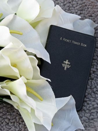 pocket prayer book with lilies, symbols of funeral ceremony photo