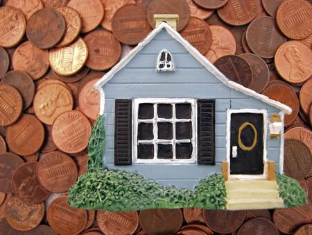 a toy house sitting on many pennies photo