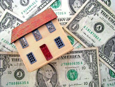 a toy house sitting on dollar bills photo