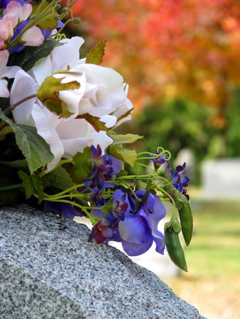silk flowers on a cemetery grave headstone