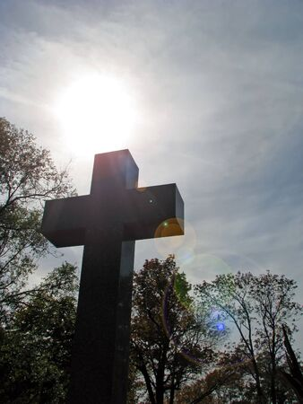 bright sun shining behind christian cross silhouette
