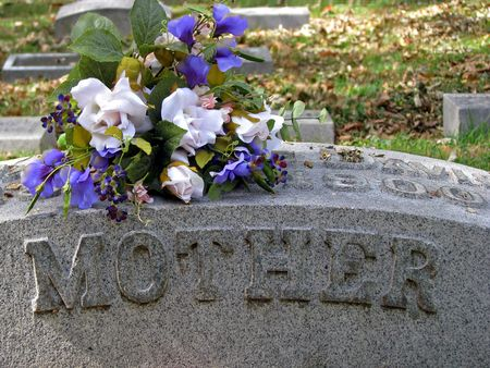 silk flowers on a cemetery grave headstone mother