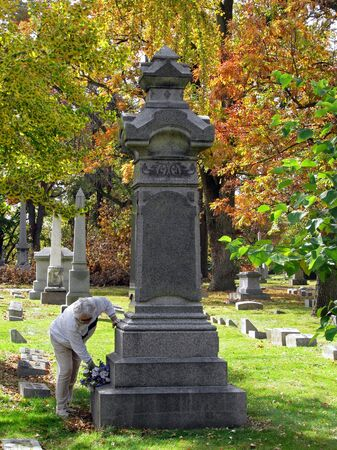 woman putting silk flowers on cemetery headstone photo