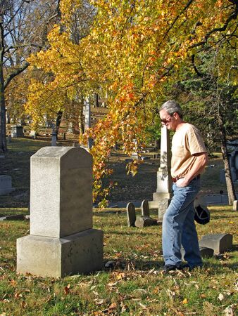 gravesite: man in old historic cemetery with colorful autumn trees
