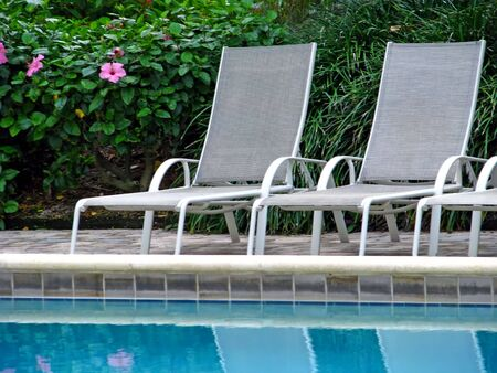 empty chaise lounge chairs reflecting in pool
