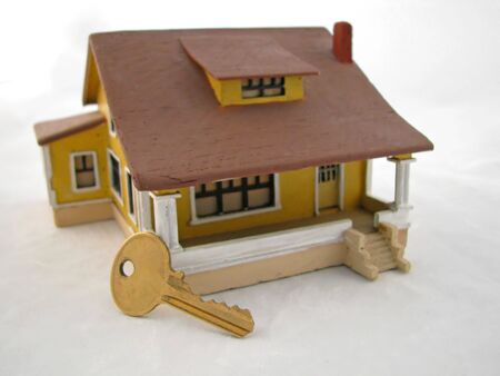 house key leaning against toy model home photo