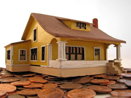 많은 동전에 앉아있는 장난감 집