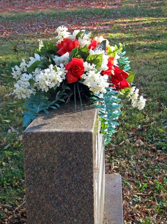 tribute: silk flowers on a cemetery grave headstone