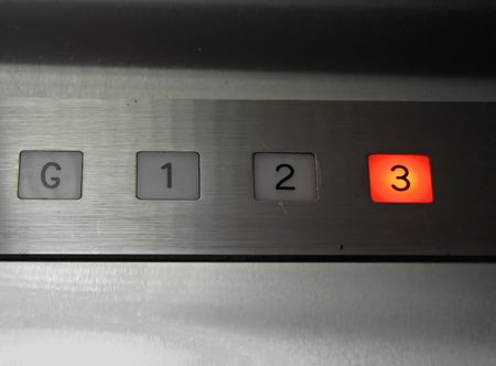metal buttons: inside of old elevator number 3 floor pushed Stock Photo