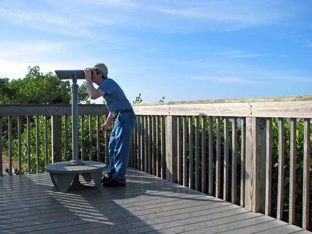 man exploring Florida wildlife refuge with spyglass Stok Fotoğraf