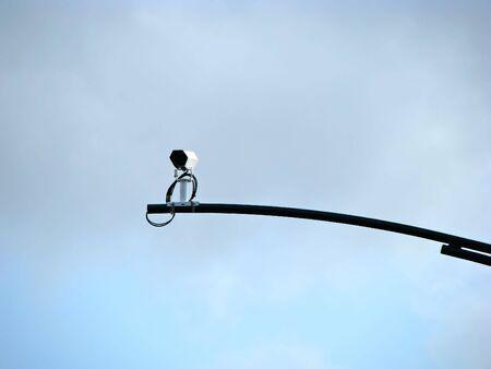 a traffic camera against pale blue sky photo