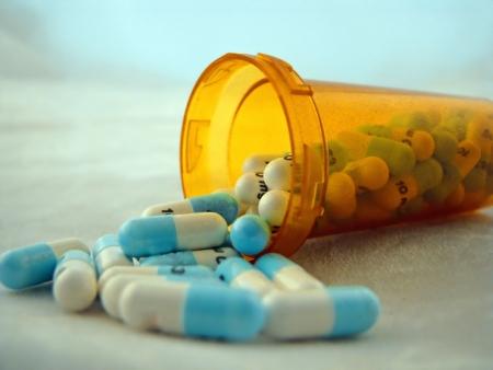 generic drugs: aprire una bottiglia di fuoriuscito capsula farmaci pillole Archivio Fotografico