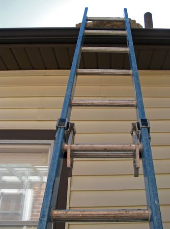aluminum: tall ladder on house reaching to roof Stock Photo