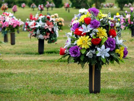 colorful silk flower vases in summer cemetery