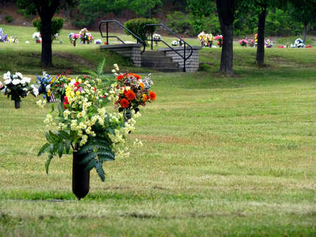 grave site: colorful silk flower vases in summer cemetery