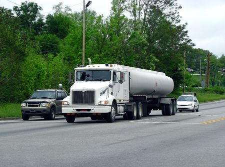 big fuel tanker truck in street traffic photo